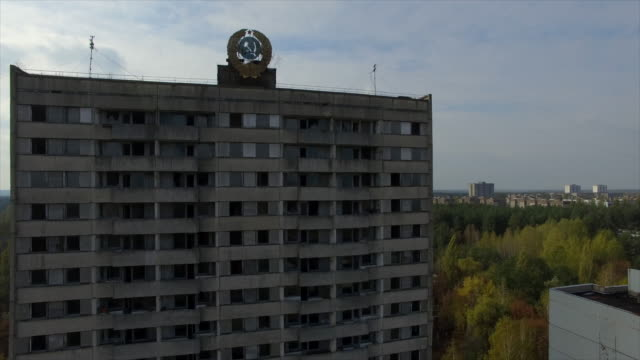 """""""let atom be a worker, not a soldier"""" slogan on building. coat of arms of ussr on building in pripyat -- abandoned town near chernobyl nuclear power plant - 1985 stock videos & royalty-free footage"""