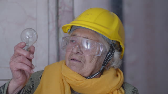 let it be led. light bulb evolution. close-up portrait of an active senior electrician making her choice for the future. experienced professional - safety equipment stock videos & royalty-free footage