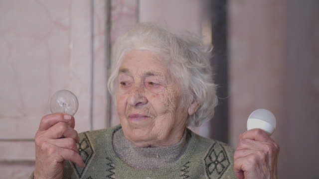 let it be led. light bulb evolution. close-up portrait of an active senior woman making her choice for the future. real people life. - electricity stock videos & royalty-free footage