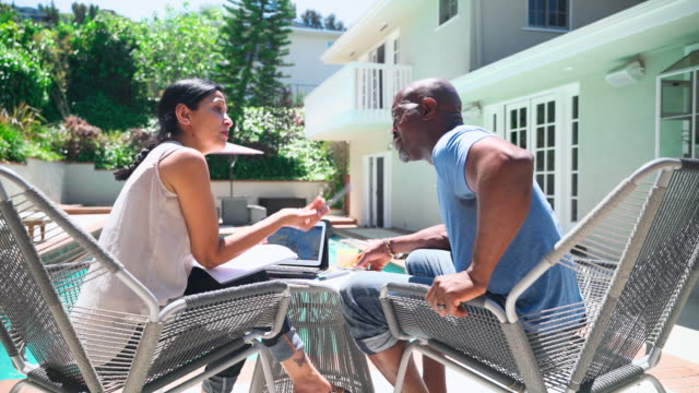 reden wir über finanzen! das ältere rentnerpaar, ehefrau und ehemann, saß draußen neben dem pool, trinkt den orangensaft und spricht über pensionsplan und finanzielle investitionen, mit den gedruckten dokumenten und dem tablet. - pc stock-videos und b-roll-filmmaterial