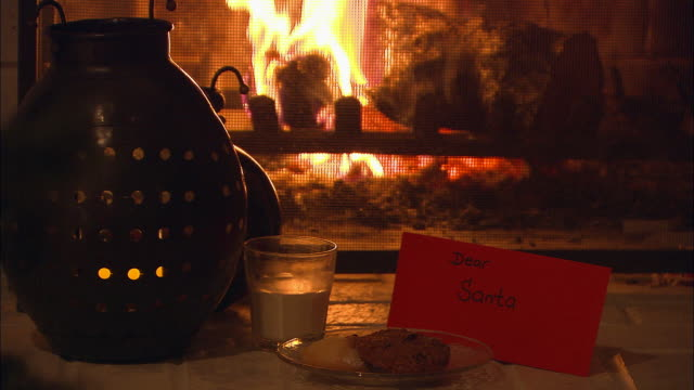 CU, Letter to Santa with Christmas cookies and glass of milk next to fireplace