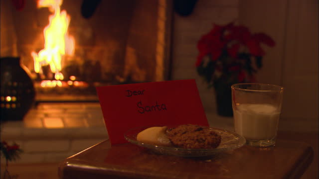 CU, Letter to Santa with Christmas cookies and glass of milk on table, fireplace in background