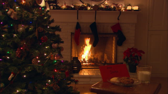vidéos et rushes de ms,  letter to santa with christmas cookies and glass of milk on table next to christmas tree, fireplace in background - noël