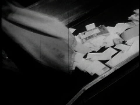 1957 ms letters being dumped onto conveyor belt / united states - sack stock-videos und b-roll-filmmaterial