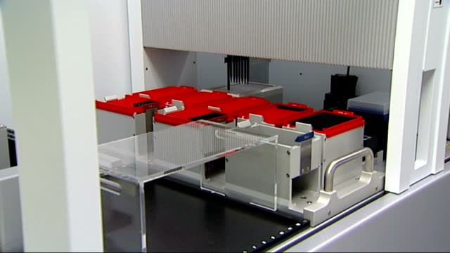 new spit test to find bone marrow donors laboratory england london int machine in laboratory placing samples into vials for testing / technicians and... - osso video stock e b–roll