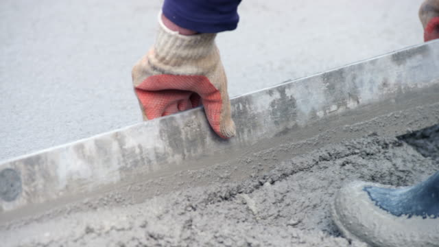 leveling the fresh concrete with a long leveling tool - cement stock videos & royalty-free footage