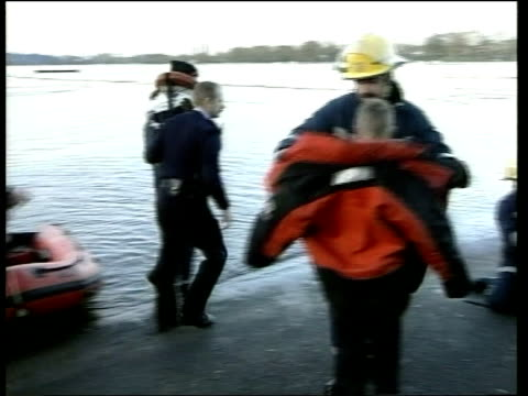 rescue near worcester; itn england: worcester: worcester race course: ext firefighters out of dinghy with three of the five boys bv police officer... - itv late evening bulletin点の映像素材/bロール