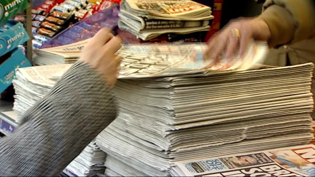 stockvideo's en b-roll-footage met main political parties reach agreement on new system of press regulation woman buying copy of daily mirror newspaper from newsstand - daily mirror