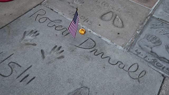 levi tinker, of tcl chinese theatre places flags on the stars, hand and foot prints for veterans day honoring hollywood stars who served in the u.s.... - tcl chinese theatre stock videos & royalty-free footage