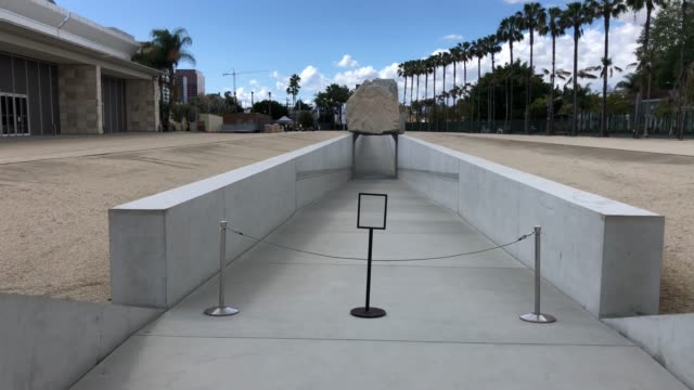 levitated mass at lacma, a usually popular and crowded los angeles tourist attraction closed at 3pm on march 17, 2020 in los angeles, california. - ロサンゼルスカウンティ美術館点の映像素材/bロール