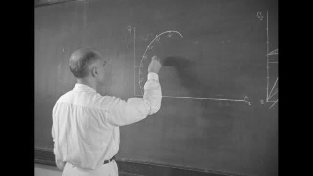 lewis holy name school / building with words lewis holy name school of aeronautics / young man looking at inscription george cardinal mundelein 1934... - italienischer abstammung stock-videos und b-roll-filmmaterial