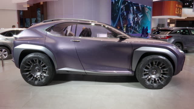 vídeos de stock e filmes b-roll de ws lexus wall logo zo tilt down to ws ux concept / ws lexus ux concept revolving on turntable / ms front fender dolly out and ped up to ws ha looking... - ametista