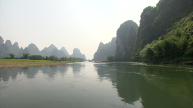 WS POV Li River with silhouetted mountains in distance, Guilin, Guangxi Zhuang Autonomous Region, China