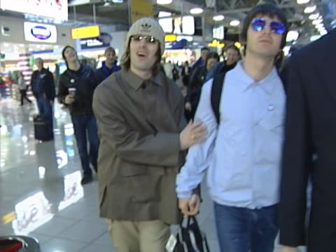 vídeos de stock e filmes b-roll de liam gallagher jokingly strokes brother noel in display of brotherly love as they fly from heathrow to tokyo amidst rumours of band split - irmão