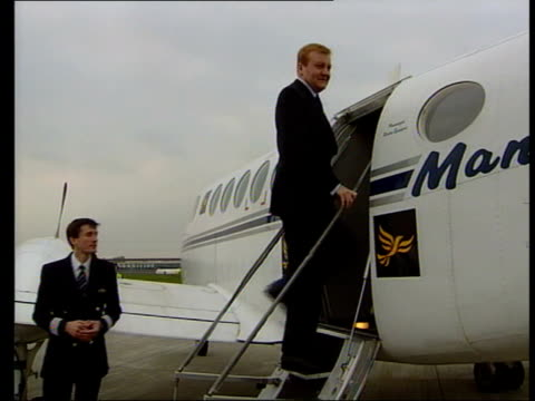ext liberal democrat leader charles kennedy getting onto plane int kennedy sat on plane reading papers ext kennedy out of plane - charles kennedy stock videos & royalty-free footage