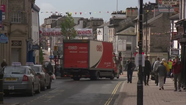 stockvideo's en b-roll-footage met interview tim farron england cumbria kendal gvs of town including clock tower union jack flag flying town centre with traffic and people along /... - street name sign