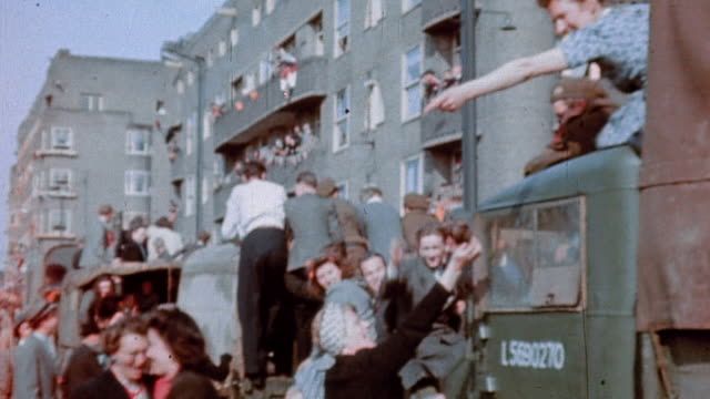 stockvideo's en b-roll-footage met liberated civilians welcoming canadian army soldiers in trucks / amsterdam, the netherlands - tweede wereldoorlog