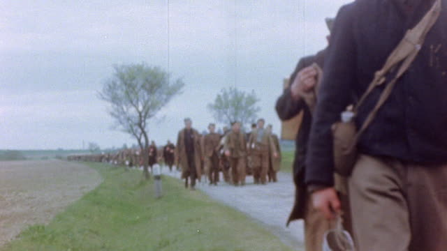 liberated french prisoners and laborers marching along road and through village and captured german army soldiers wading across a shallow stream... - 水につかる点の映像素材/bロール