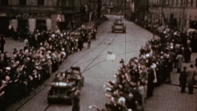 liberated villagers cheering and waving on side of road as convoy of us army jeeps and m4 sherman tanks drive through / pilsen czech republic - ve day stock-videos und b-roll-filmmaterial