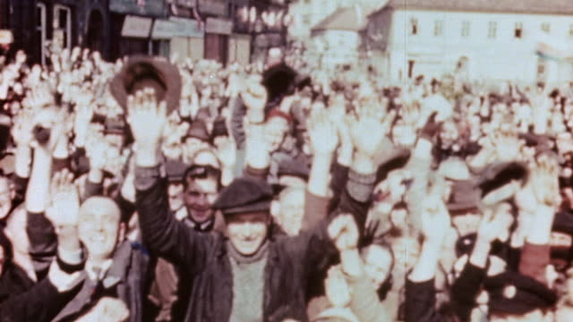 pan liberated villagers gathered in front of town buildings waving and welcoming american troops / pilsen czech republic - ve day stock-videos und b-roll-filmmaterial