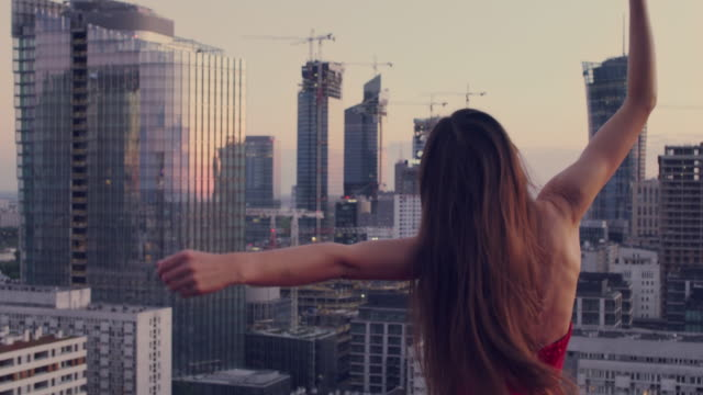 stockvideo's en b-roll-footage met bevrijde vrouw die op een dak danst. het dragen van rode, fabelachtige kleding die stadspanorama bewondert - avondjurk