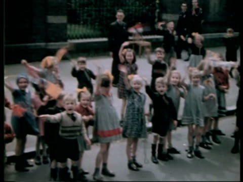 stockvideo's en b-roll-footage met liberation of amsterdam, children waving on street / amsterdam, noord-holland, netherlands - tweede wereldoorlog