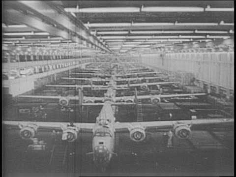 liberator bomber plane flying under title / long shot of ford's willow run aircraft plant in michigan / overhead tracking shot of b-24 bombers on... - production line点の映像素材/bロール