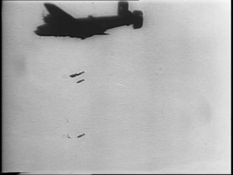Liberator bomber plane release multiple bombs on target below / enemy v1 rocket bomb explodes from typhoon rocket attack slow motion of same shot /...