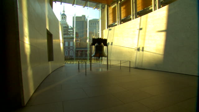 liberty bell center w/ bell in center of room shadows sunlight glass wall partial independence hall w/ scaffolding two highrises bg iconic tourism... - independence hall stock videos & royalty-free footage