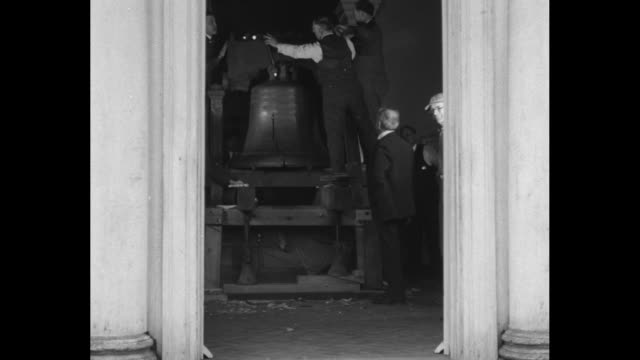 liberty bell hangs from heavy wooden yoke / ext independence hall / men seen through doorway attending to the bell / vs men unscrew and disengage... - independence hall stock videos and b-roll footage