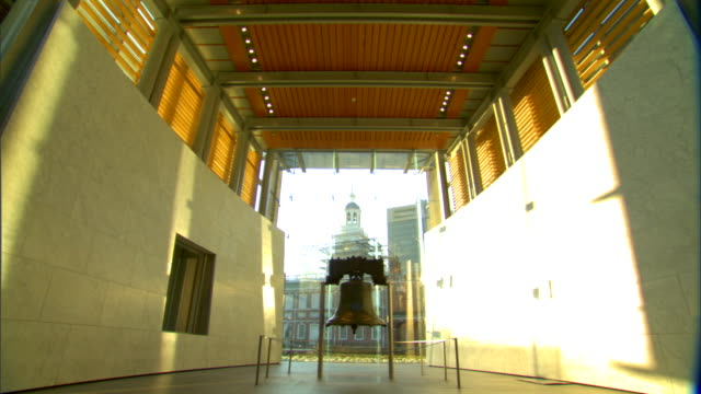 liberty bell in middle of liberty bell center shadows sunlight glass wall independence hall w/ scaffolding bg slo td iconic tourism american history... - independence hall stock videos and b-roll footage