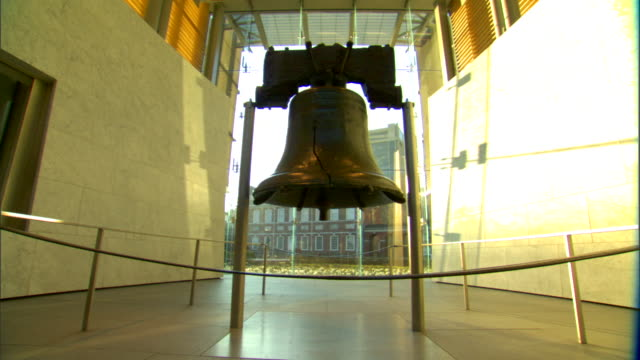 ms liberty bell in middle of liberty bell center shadows sunlight glass wall partial independence hall w/ scaffolding moving vehicles bg iconic... - liberty bell stock videos & royalty-free footage