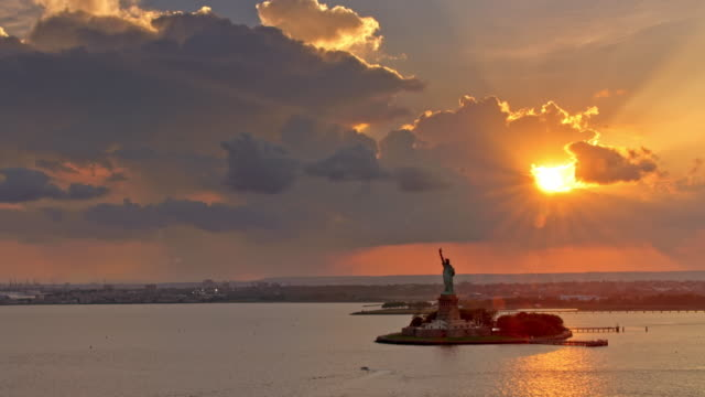 vídeos de stock e filmes b-roll de aerial liberty island with setting sun peeking through the clouds in the background - estátua