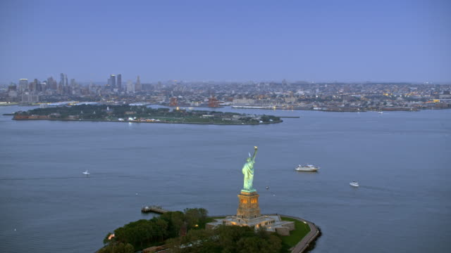 aerial liberty island with statue of liberty and new york in the evening - new york harbor stock videos & royalty-free footage