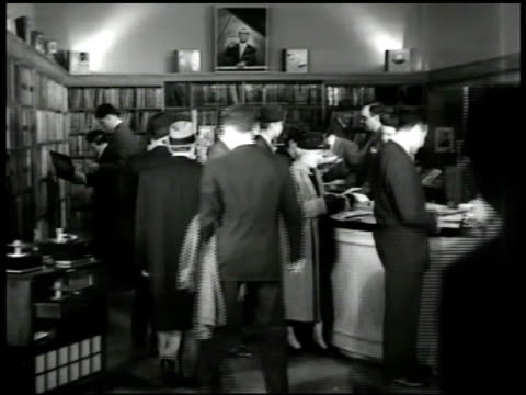 stockvideo's en b-roll-footage met ws 'liberty music shops' building int ws customers shopping for records ms customers talking at counter vs young salesman showing women record from... - 1949