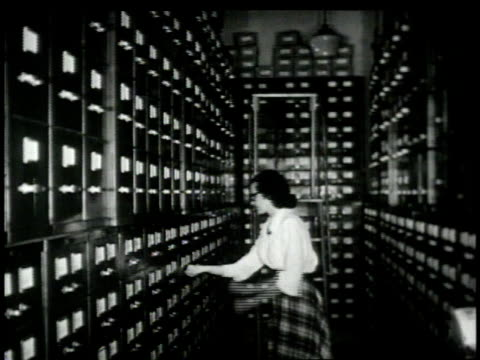 1948 MONTAGE Librarian sorting through old news clippings in reference library / New York City, New York, United States
