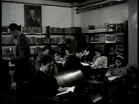 stockvideo's en b-roll-footage met library entrance 'u.s.i.s.' int turkish people reading in library. man picking up magazine 'life time' on shelf. young people reading at table man... - magazine