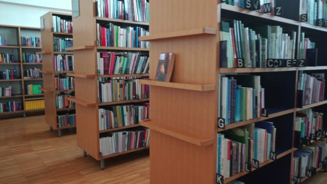 library footage - bookshelf loaded with books, marked in alphabetical order - library stock videos & royalty-free footage