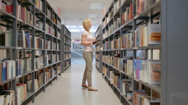 DS bibliotheek gebruikers die zoeken naar boeken in de gangpaden