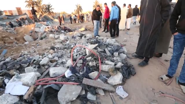 vídeos de stock e filmes b-roll de libyans gather next to debris at the site of a daesh militants training camp targeted in a us air strike near the libyan city of sabratha on february... - ataque aéreo