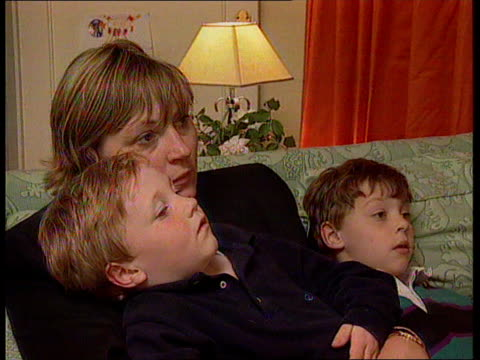 licence fee may be raised to fund bbc digital; england: london: int cms two children sitting with mother watching tv cms hand puts swipe card into... - bericht film und fernsehen stock-videos und b-roll-filmmaterial