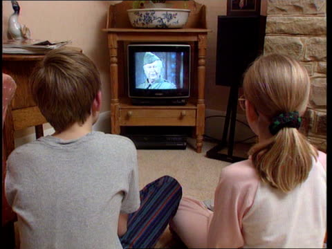 tv licence fee may be raised to fund bbc digital int bv two children sitting on floor watching tv - fee stock videos & royalty-free footage