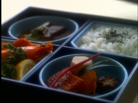 stockvideo's en b-roll-footage met lid being removed from lunch box with japanese foods - vier dingen