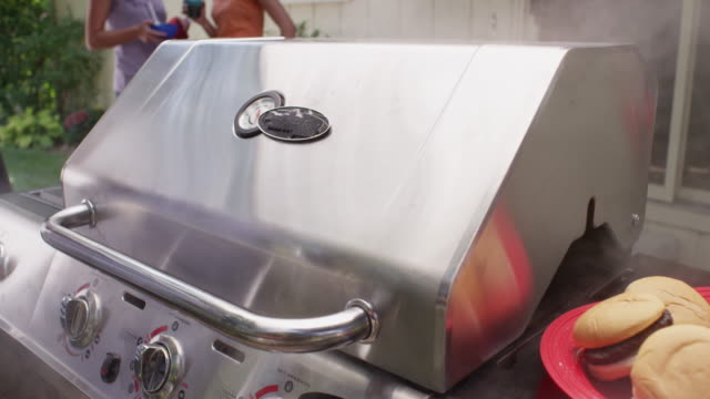 lid is closed on an outdoor grill which is smoking like crazy. - lid stock videos and b-roll footage