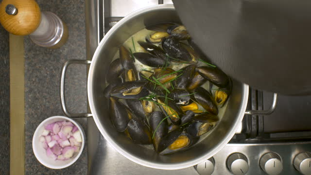 lid is removed to reveal mussels cooking in a saucepan. moules mariniere. - mollusc stock videos & royalty-free footage