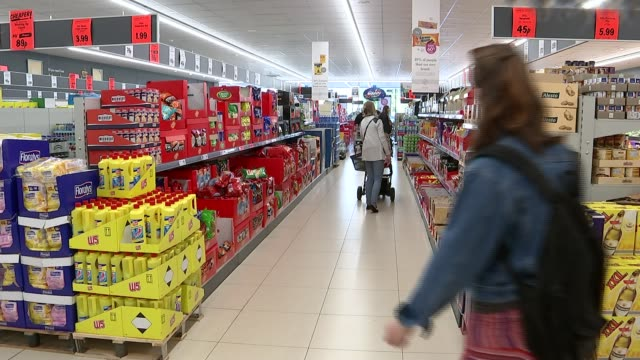 Lidl to pay workers the living wage INT Customer pushing trolley away at Lidl supermarket Shoppers in Lidl supermarket Zahid Nawaz interview SOT...