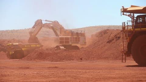 vidéos et rushes de liebherr international deutschland gmbh excavator loads iron ore onto a caterpillar inc 793f autonomous haul truck at the kings mine site at... - caterpillar inc.