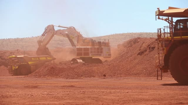 a liebherr international deutschland gmbh excavator loads iron ore onto a caterpillar inc 793f autonomous haul truck at the kings mine site at... - iron ore stock videos & royalty-free footage