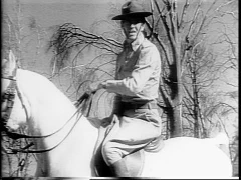 Lieutenant Dick Ryan climbing on Emperor Hirohito's horse / Ryan rides horse past crowd in stadium / close up of Japanese children in audience / Ryan...
