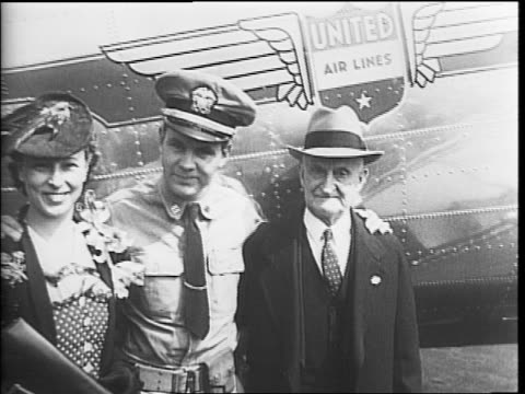 lieutenant john d bulkeley exiting an airplane greeted by his wife and father / bulkeley with his wife and father / bulkeley walking with his family... - furlough stock videos & royalty-free footage